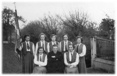 Jonge KVLV-vrouwen poseren met pastoor.
