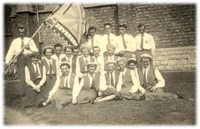 Groepsfoto van dames en heren met Zevergems vaandel.