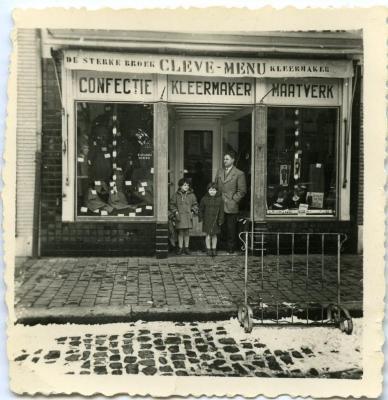 Albert Cleve poseert met zijn kinderen voor zijn kleerwinkel De sterke broek