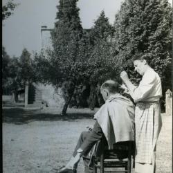 Marie Minne knipt het haar van Edgar Gevaert in de tuin